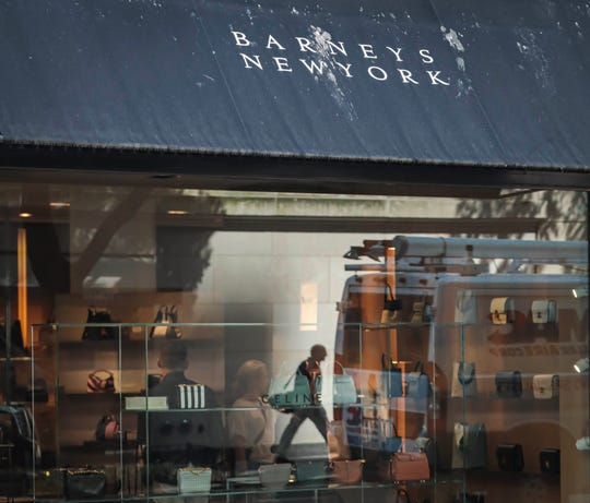 In this July 16, 2019, file photo a pedestrian reflect in a store window at Barneys department store in New York. Barneys New York, which opened its 10-story Madison Avenue store in 1993, became a cultural icon in luxury shopping but now risks closure.