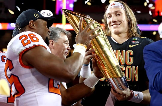 Clemson quarterback Trevor Lawrence  celebrates with the national championship trophy after the Tigers beat Alabama in the College Football Playoff championship game.
