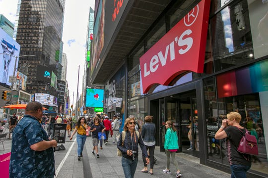 In this June 14, 2019, photo people pass the Levi's store in in New York's Times Square.