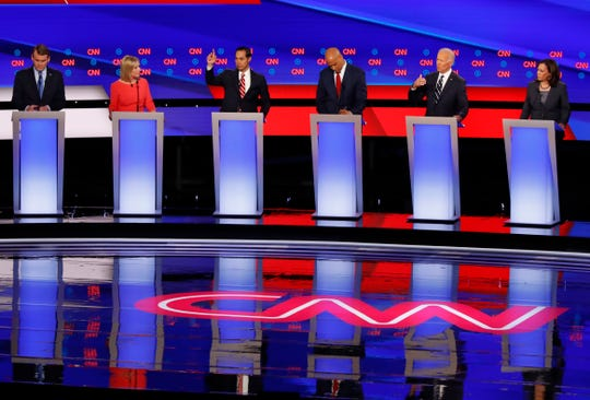 From left, Sen. Michael Bennet, D-Colo., Sen. Kirsten Gillibrand, D-N.Y., former Housing and Urban Development Secretary Julian Castro, Sen. Cory Booker, D-N.J., former Vice President Joe Biden and Sen. Kamala Harris, D-Calif., participate in the second of two Democratic presidential primary debates hosted by CNN Wednesday, July 31, 2019, in the Fox Theatre in Detroit. (AP Photo/Paul Sancya)