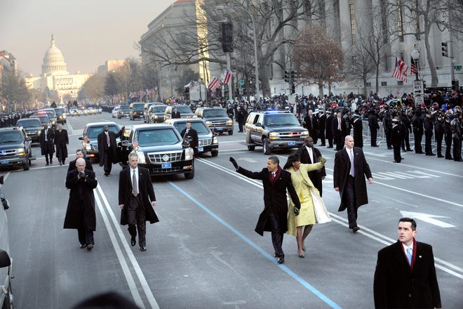 President Barack Obama and first lady Michelle Obama wave to the crowd during the inaugural parade on Jan. 20, 2009.