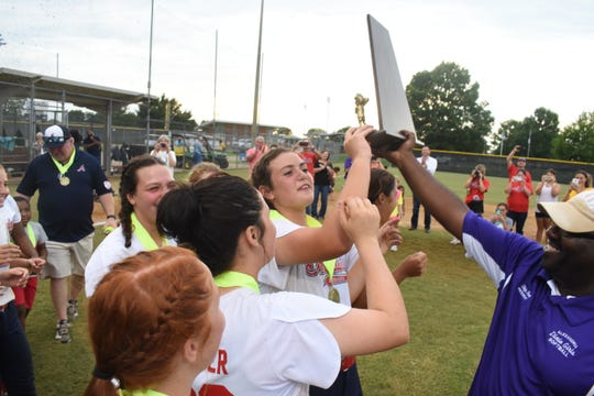 Alexandria Dixie Girls Softball President Skip Fox (right) hands the Dixie League World Series championship trophy to the Alexandria Belles after their win over Georgia Thursday.