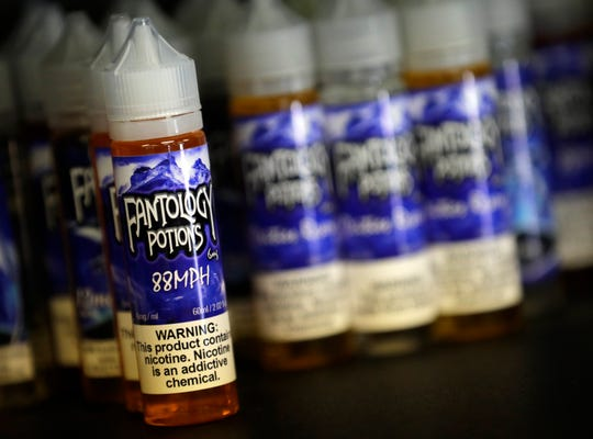A warning label marks an e-liquid product at NAH Vapor & Glass in Neenah.