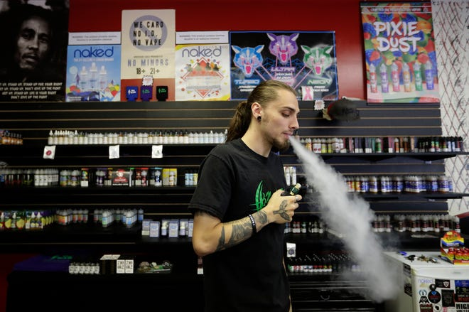 Colton Schwandner, owner of NAH Vapor & Glass, vapes in his shop while waiting for customers Friday in Neenah.