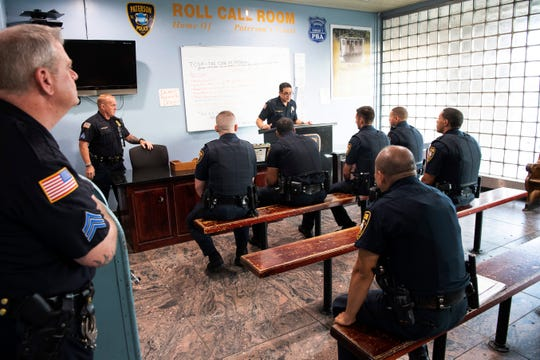 (center) Paterson Police Shift Supervisor Lt. Donato DeAngelis leads the 7 a.m. roll call at Paterson police headquarters on Thursday, August 2, 2019.