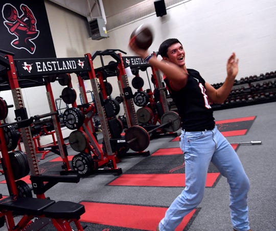 Behren Morton throws the football to an Eastland Mavericks teammate inside the high school's weight room August 1.