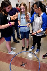 Emily McKinney, center, listens as fellow eighth-graders Cloie Huntley, left, and Vivian Pham advise her on how to fly a drone on April 4. Wylie Junior High School was holding an open house for students interested in coding, gaming, robotics and innovation.