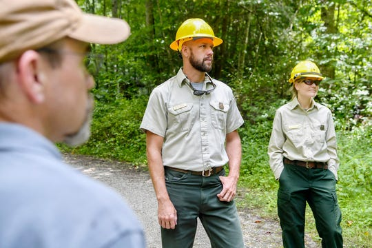 Jason Herron, environmental coordinator with the U.S. Forest Service's Pisgah Zone, center, and Tara Anderson, wildlife biologist for the Forest Service's Pisgah Zone, stand along Fall Branch Road as they tour areas of the Twelve Mile Project July 24, 2019.