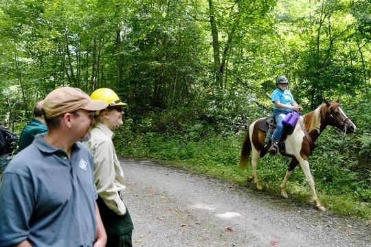 A horseback rider passes by near the Harmon Den Horse Camp along Fall Branch Road July 24, 2019.