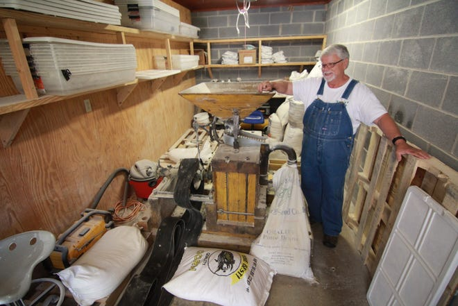 Bill Welsch of The Lord's Harvest grinds corn for the cornmeal included in a typical food distribution box.