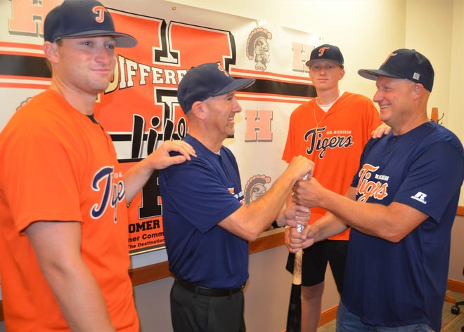 Mid-Michigan Tigers manager Jeff Sherman, right, and interim manager Scott Salow have some fun by pretending to see who 'gets the upper hand' on the bat as to who will manage the team in the World Series. Sherman won't be available to coach the team and has asked state championship coach Salow to step in. They are joined by Mid-Michigan Tigers player Preston Sherman, left, and Jordan Sherman, who obviously are wondering what is going on.