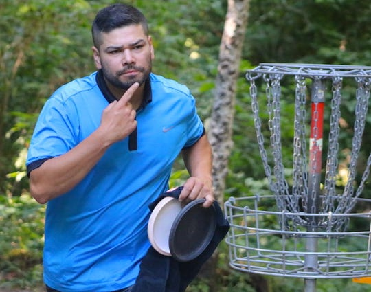 Christian Vasquez uses sign language after finishing the 18th hole during play Thursday at the Deaf Disc Golf Association national tournament at NAD Park in Bremerton.