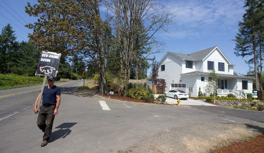 Islander Jim Halbrook paces back and forth outside the Reserve at Winslow, protesting the new development on Finch Road on Bainbridge Island.