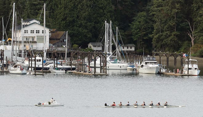 FILE PHOTO - Rowers pass the Eagle Harbor Marina on Bainbridge Island on Thursday, August 1, 2019.