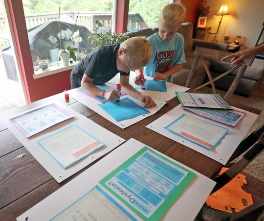 Evan Hempler, 9, right, and his younger brother David, 7, glue graphics to poster board. Evan is looking to expand people's awareness of dyslexia.