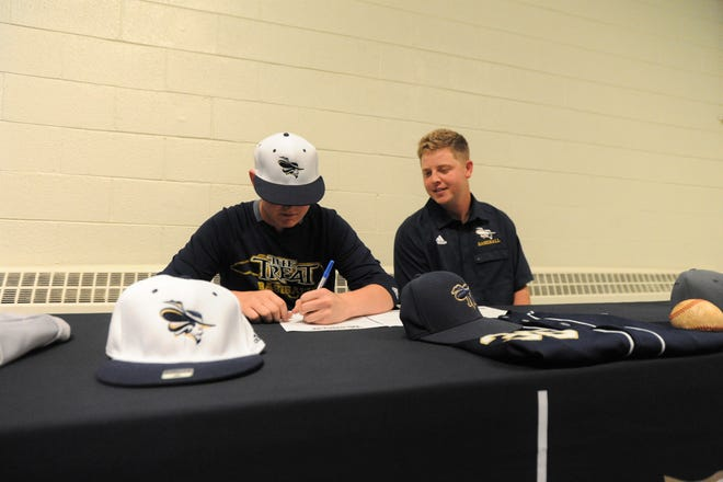 Trenton Messer signs to play baseball for Montreat College on July 30 as Cavaliers assistant coach Grayson Snipes looks on.