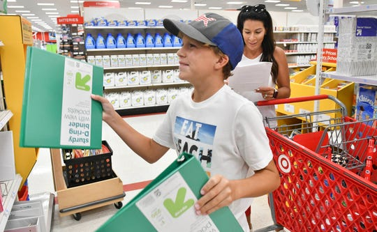 Joey Romine, 12, and his mother Melissa shop for school supplies at Target in Viera Friday afternoon.