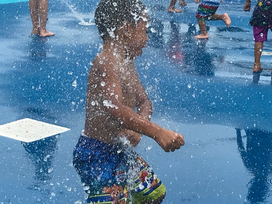 Jyair Johnson, 4, plays in the water at the newly-renovated park at 4th and Washington streets in Camden.