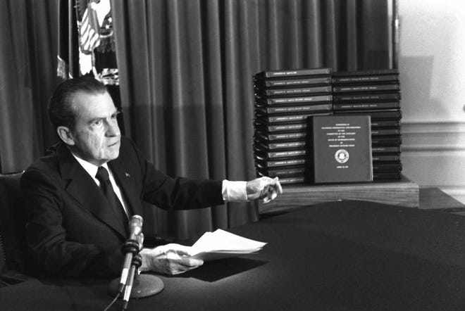 President Richard Nixon gestures toward transcripts of White House tapes after announcing he would turn them over to House impeachment investigators.