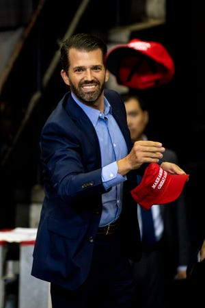 """Donald Trump Jr. throws """"Make America Great Again"""" hats to the crowd at the """"Keep America Great"""" campaign rally Thursday, August 1, 2019 at U.S. Bank Arena in downtown Cincinnati."""