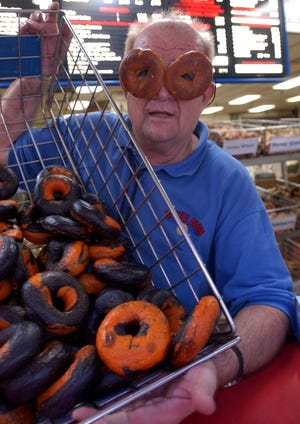 Sept. 12, 2003: John Marx, owner of Marx Bagels, holds a batch of orange and black Bengal Bagels at his shop in Blue Ash.