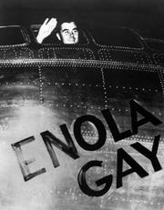 Col. Paul W. Tibbets Jr., pilot of the Enola Gay, the plane that dropped the atomic bomb on Hiroshima, waves from the cockpit before takeoff on August 6, 1945.
