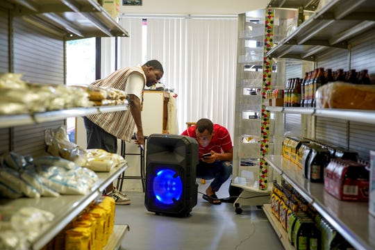 Adolph Dagan, left, and Florentin Gamé work to set up a speaker system to play music Aug. 1, 2019, at Dagan African Market on Fort Campbell Boulevard in Clarksville, Tenn.