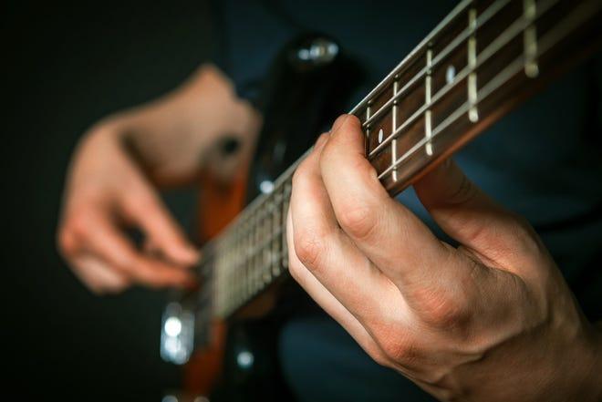 Closeup of rock guitarist practicing with bass guitar.