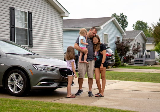 Tommy Wolikow poses for a photo with his daughters (left to right) Ali Jenkins, 7, Bella Wolikow, 18-months and Natalie Wolikow, 11, at his mobile home in Swartz Creek. Wolikow transferred to General Motor's Flint Assembly and commutes back to his actual home in Lordstown weekly.