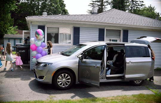 In this Tuesday, July 16, 2019, photo, Melanie Matcheson, right, unloads her Chrysler Pacifica as her son Alexander and daughters Keiley, Caroline, and Georgianna head back into the house in Cheshire, Connecticut.