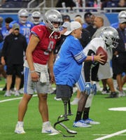 Calder Hodge, 13, takes the snap next to Lions quarterback Matthew Stafford, and runs a play with the team Friday at Ford Field.