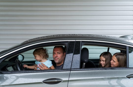 Tommy Wolikow poses for a photo with his daughters (left to right) Bella Wolikow, 18 months, Ali Jenkins, 7, and Natalie Wolikow, 11, in his car on Monday, July 29, 2019 at his mobile home in Swartz Creek. Wolikow transferred to General Motor's Flint Assembly and commutes back to his actual home in Lordstown weekly.