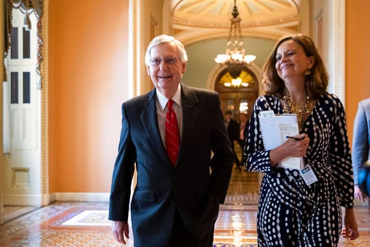 Senate Majority Leader Mitch McConnell, R-Ky., accompanied by Sharon Soderstrom, his chief of staff, smiles after a vote on a hard-won budget deal that would permit the government to resume borrowing to pay all of its obligations and would remove the prospect of a government shutdown in October, at the Capitol in Washington, Thursday, Aug. 1, 2019.