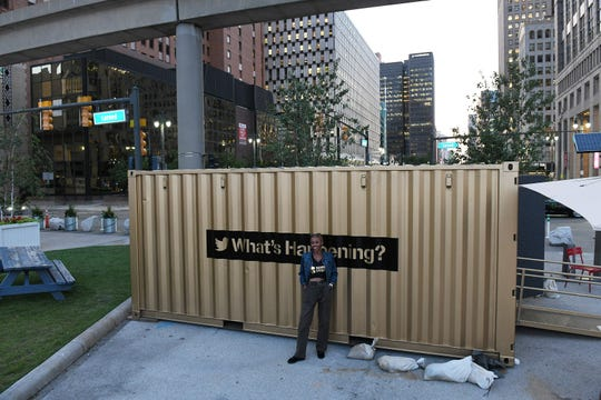 While her mother takes a photo, curator Hannah Morris of Southfield stands by the shipping container turned into a studio at Spirit Plaza in Detroit.