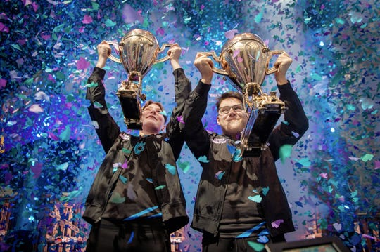 "In this Saturday, July 27, 2019 photo, provided by Epic Games, Emil ""Nyhrox"" Bergquist Pedersen, of Norway, left, and David ""Aqua"" Wang, of Austria, hold up their trophies after winning the Fortnite World Cup duo championship in New York."