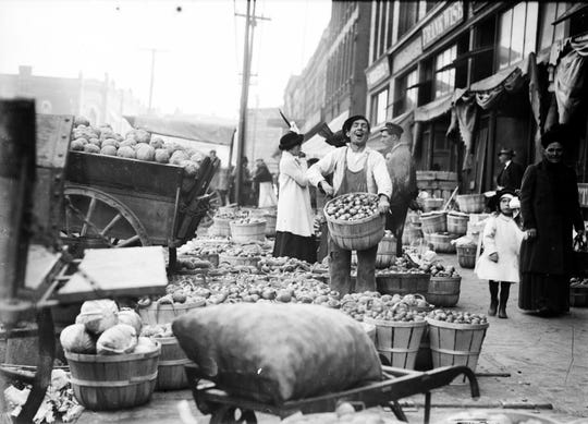 A farmer displays his potatoes and cabbages at Eastern Market in the early 20th century.