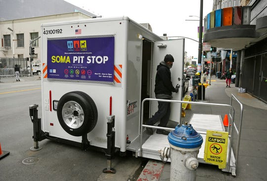 "An attendant exits a ""Pit Stop"" public toilet on Sixth Street, Thursday, Aug. 1, 2019, in San Francisco. A 5-year-old portable toilet program in San Francisco that provides homeless people with a private place to go has expanded to 25 locations in the city and has spread to Los Angeles."