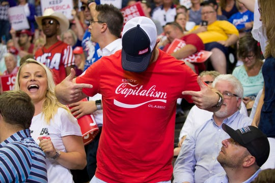 A supporter points to his shirt before President Donald Trump speaks at a campaign rally Thursday, Aug. 1, 2019, in Cincinnati.