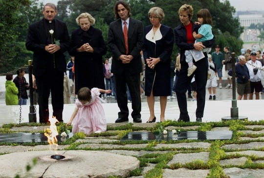 FILE - In this June 6, 2000 file photo, Robert F. Kennedy's granddaughter Saoirse Kennedy Hill places a white rose at the Eternal Flame, President John F. Kennedy's gravesite, at Arlington National Cemetery in Arlington, Va. Hill, has died at the age of 22. The Kennedy family released a statement on Thursday night, Aug. 1, 2019, following reports of a death at the family's compound in Hyannis Port, Massachusetts. Hill was the daughter of Robert and Ethel Kennedy's fifth child, Courtney, and Paul Michael Hill.