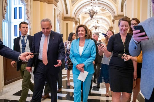 Senate Minority Leader Chuck Schumer, D-N.Y., left, joins Speaker of the House Nancy Pelosi, D-Calif., on the way to sign the budget package that had just passed in the Senate on Thursday, Aug. 1, 2019.
