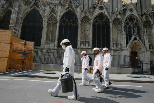 Workers dressed in white overalls walk past the Notre Dame Cathedral as the preliminary work begins to repair the fire damage.