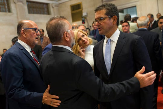 Proposed Secretary of State Pedro Pierluisi, right, is greeted by lawmakers Luis Ortiz and Jose Aponte during a break in his confirmation hearing at the House of Representatives, in San Juan, Puerto Rico, Friday, August 2, 2019.