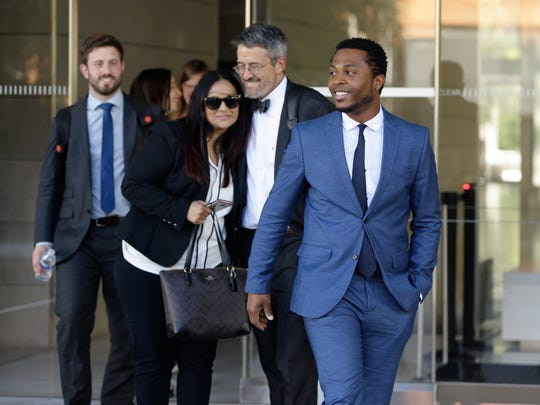 Rapper Marcus Gray, right, with his attorney, Michael A. Kahn, second from right, leave the federal courthouse in Los Angeles, Thursday, Aug. 1, 2019.