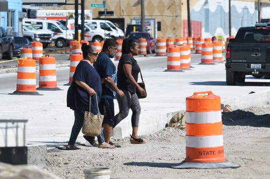 Pedestrians use caution as they cross Livernois at Chesterfield Friday, often needing to walk blocks to get to a place where they are able to cross the street.