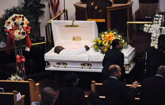 """FILE - In this July 23, 2014 file photo, Eric Garner's body lies in a casket during his funeral at Bethel Baptist Church in the Brooklyn borough of New York. On Friday, Aug. 2, 2019, an administrative judge recommended firing a New York City police officer Daniel Pantaleo, who is white, over the chokehold death of the unarmed Garner, whose dying cries of """"I can't breathe"""" fueled a national debate over policing, race and the use of force."""