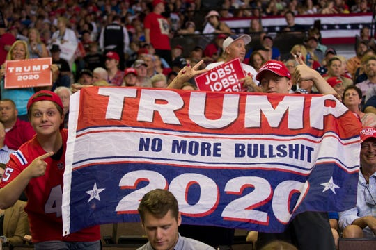 Supporters cheer and hold a flag before President Donald Trump speaks at a campaign rally Thursday, Aug. 1, 2019, in Cincinnati.