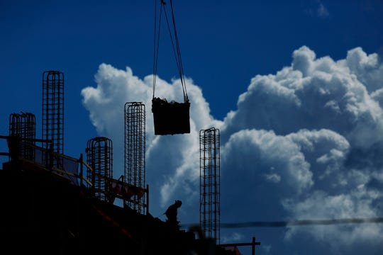 A construction worker walks atop a building as a crane lifts a load over head in Miami.