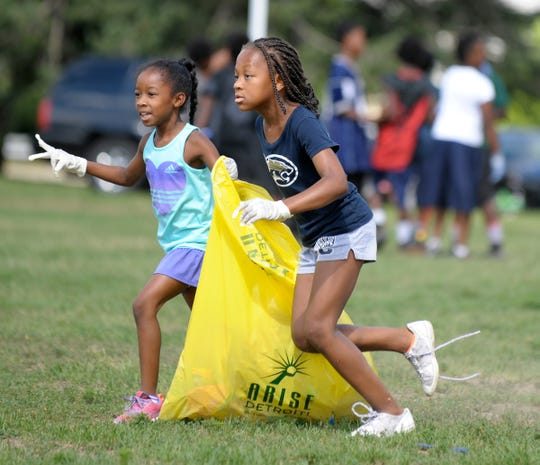 Members of the Northwest Detroit Cougars Youth Association Football and Cheer teams cleaned up sports fields behind Bates Academy as part of ARISE Detroit's Neighborhoods Day in 2016. Above, Cougars C-Team Cheerleaders Kaitlyn Henry, left, 8, of Farmington Hills, and Autumn Gilmore, 7, of Warren, pick up trash.