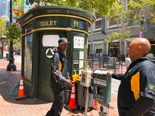 "In this photo taken July 18, 2019, Nelson Butler, right, greets Lester ""Smokey"" Williams at one of the 25 ""Pit Stop"" locations in San Francisco. The program started five years ago after children complained of dodging human waste on sidewalks on their way to school. The ""Pit Stop"" program employs recently released inmates, like Butler and Williams, to keep the bathrooms secure and clean."