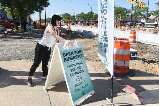 Paula Gonzales, a senior project manager in the mayor's office, sets up signs signaling businesses are open along the Avenue of Fashion on Friday.